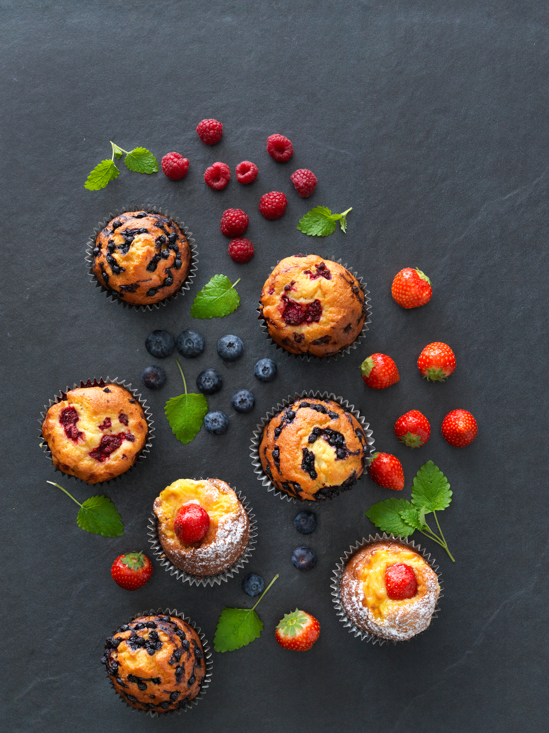 Muffins on a black table with berries